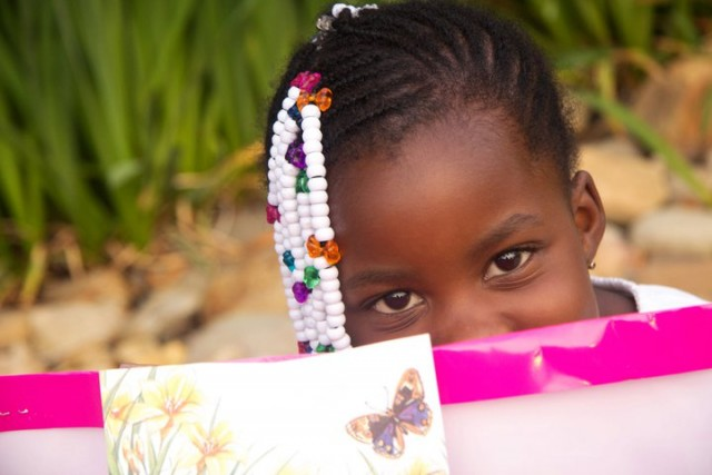 This little girl hides a happy smile from behind her birthday gift.