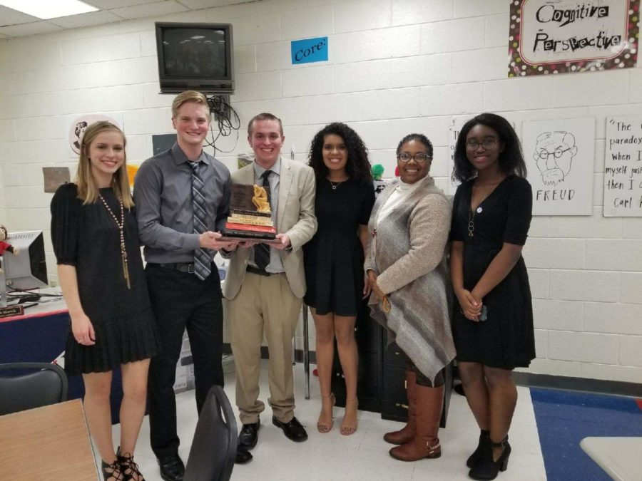 The Ethics club posing proudly with their first place trophy.