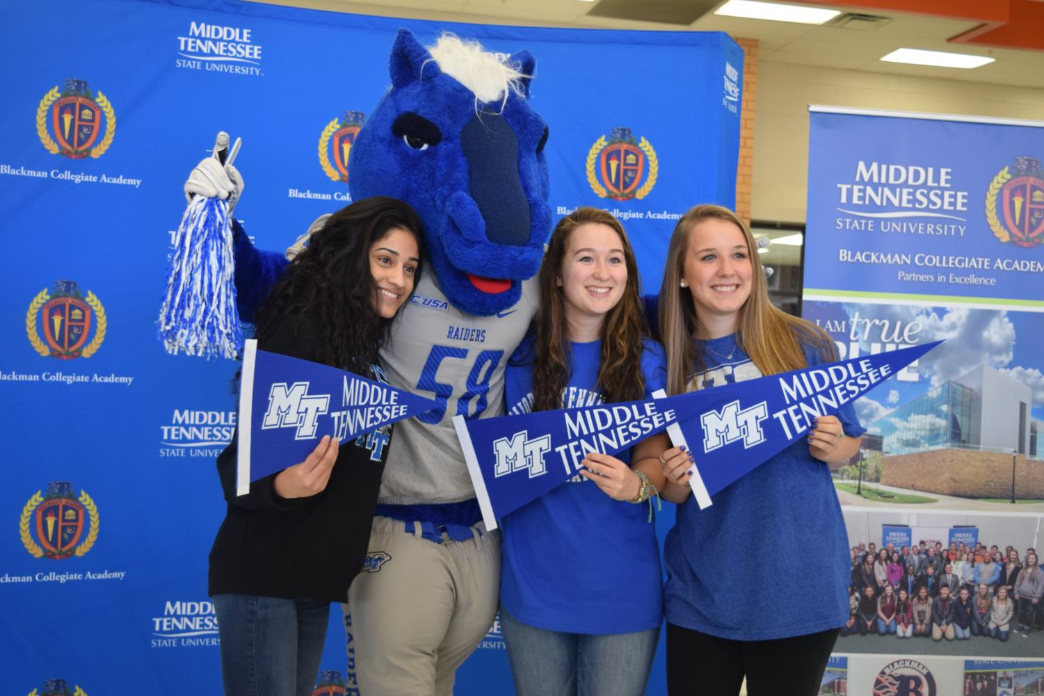 Rija+Asim+%28left%29%2C+Allison+Collins+%28middle%29%2C+and+Carly+Bowen+%28right%29+pose+with+MTSU+mascot%2C+Lightning.