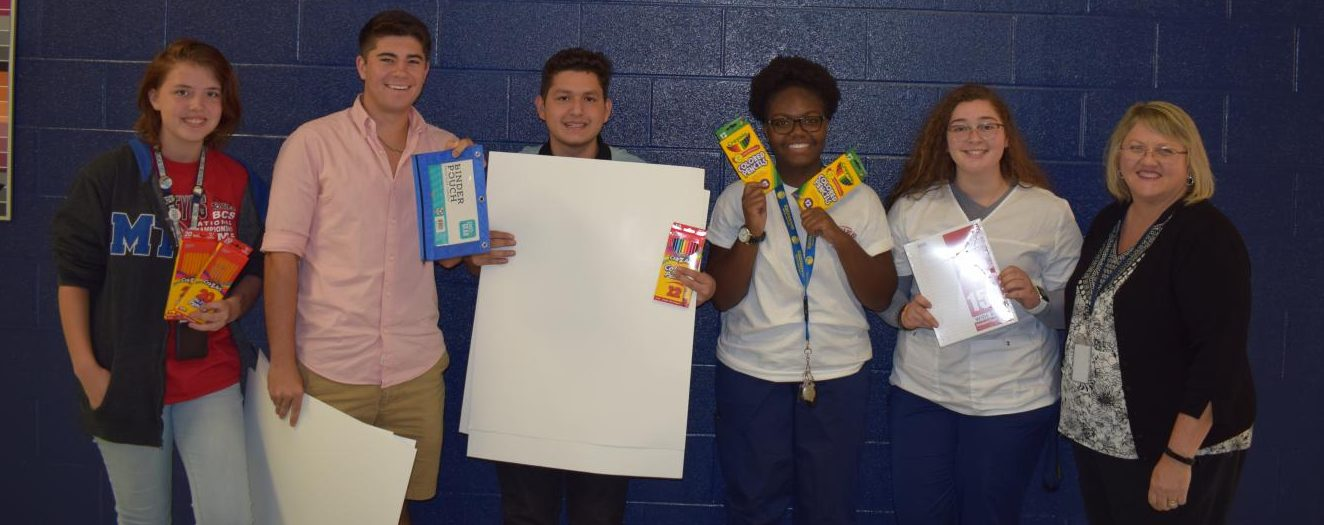 (Pictured from left to right) Morgan Stephens, sophomore; Julian Young. Carlos Coronel ,Keyah Suel, Kelsi McGregor, seniors, pictured with Kim Garrott, Atlas coordinator  Blackman Cares Club finish their school drive by giving the supplies to Garrott for Atlas students.