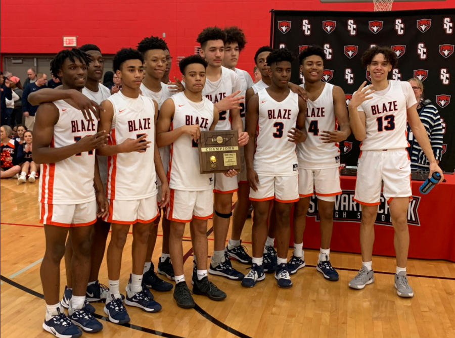 The boy's basketball team with the District Tournament trophy.