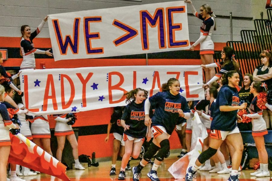 Blackman basketball cheer holding up a sign for Lady Blaze.