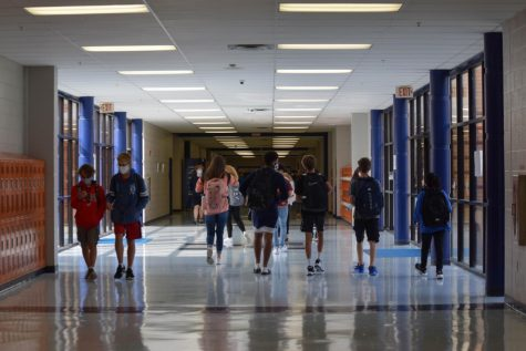 Students wear masks in the uncrowded hallway during class changes.