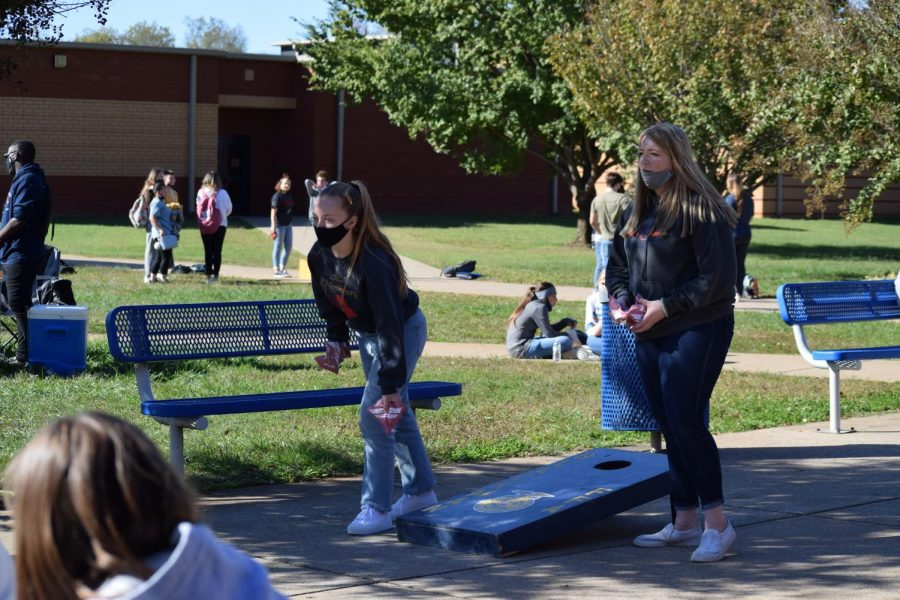 Students play cornhole in the courtyard