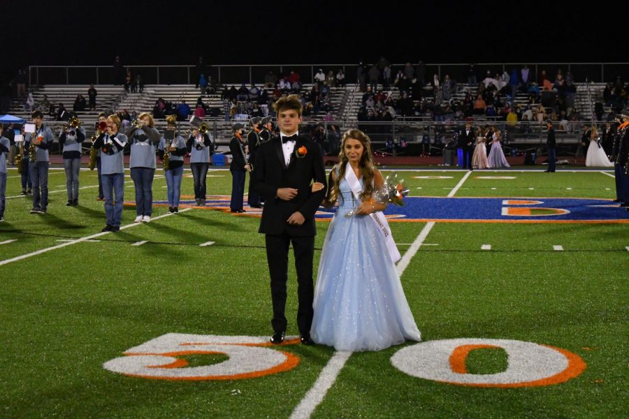 Homecoming couples line up for photographs on the field.