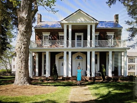 Clarissa Smith standing in front of the original Springfield home that was built in 1804, and was later renovated as a gathering place for the Springfield apartment residents.