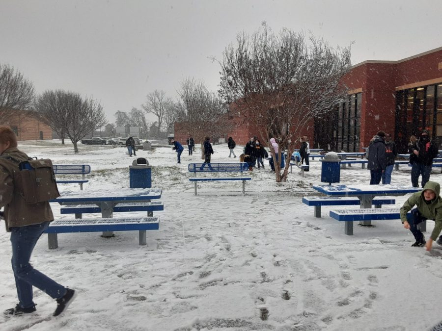 Students having a snowball fight in the courtyard.