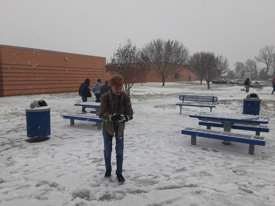 Student prepares to throw snowball at classmate.