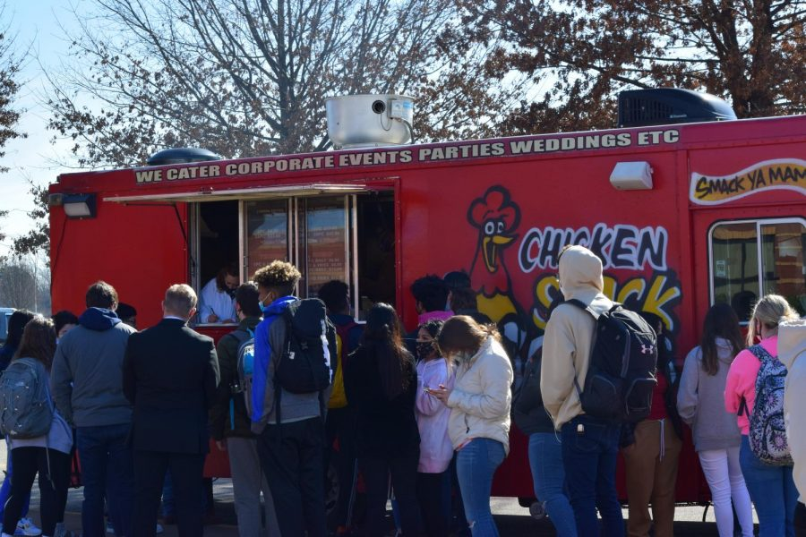 Students wait to get food at one of the food trucks at basketball homecoming for BHS.