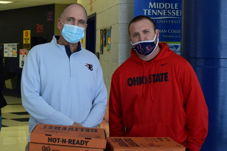Assistant Principal Scott Lawless and former head football coach Kit Hartsfield help sell pizza at the BHS basketball homecoming activities.