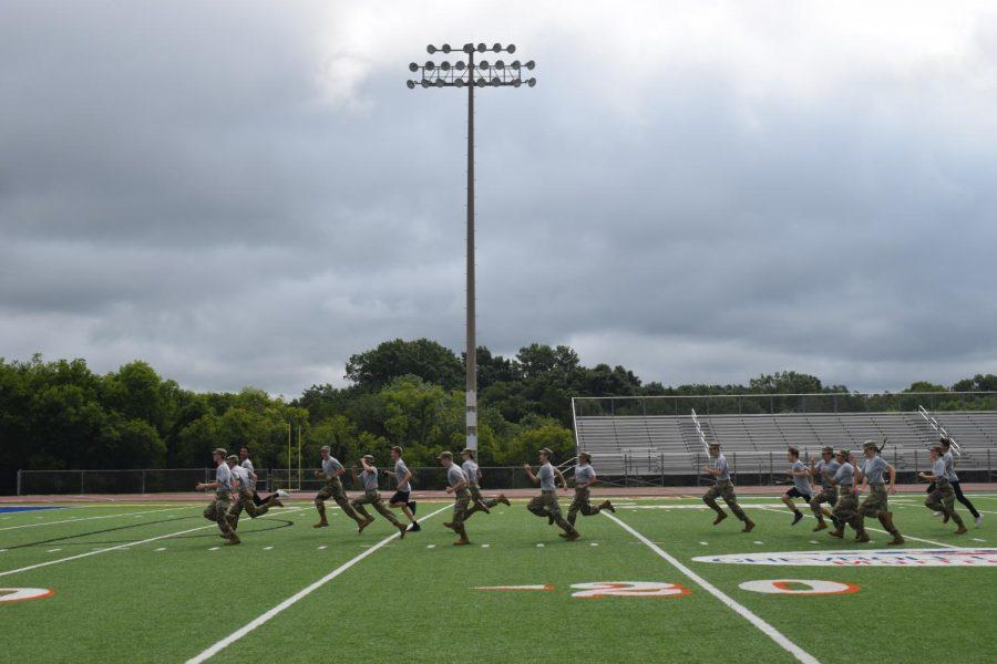 JROTC run across the football field during the first pep rally.