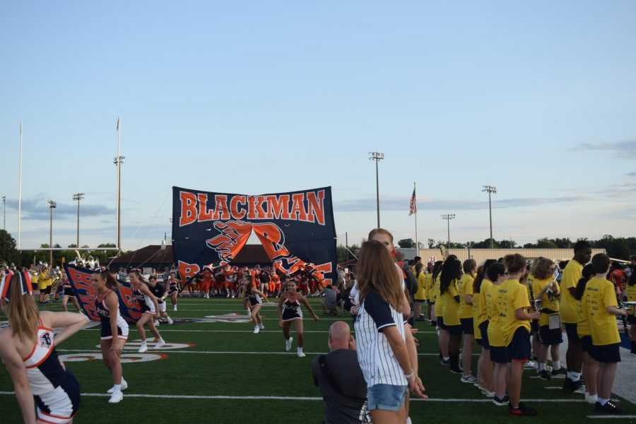 The Blackman Blaze Football team and cheerleaders running through the Blackman Blaze flag when entering the field for the first home football game.