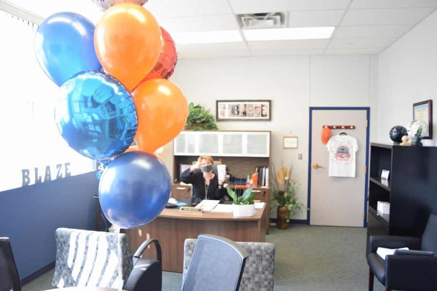Dr. Justus holds her Sonic drink behind the balloons given to administration that both came from Blackman Cares.