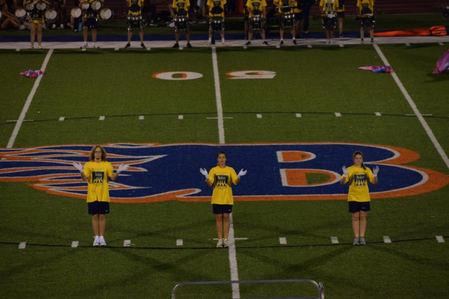 The marching band drum majors lead the halftime show.