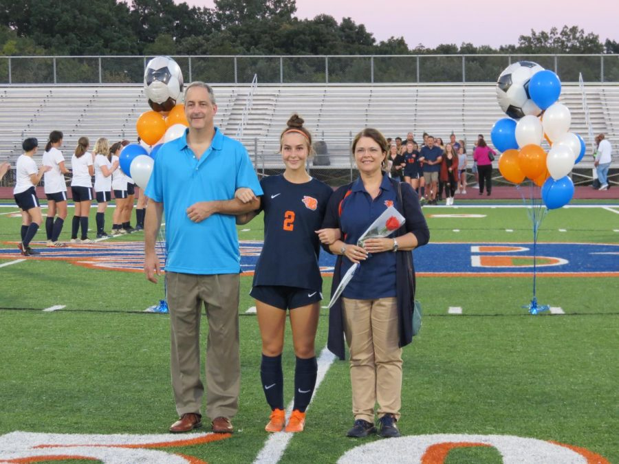 Senior Audrey Burks is escorted by her parents during senior night.