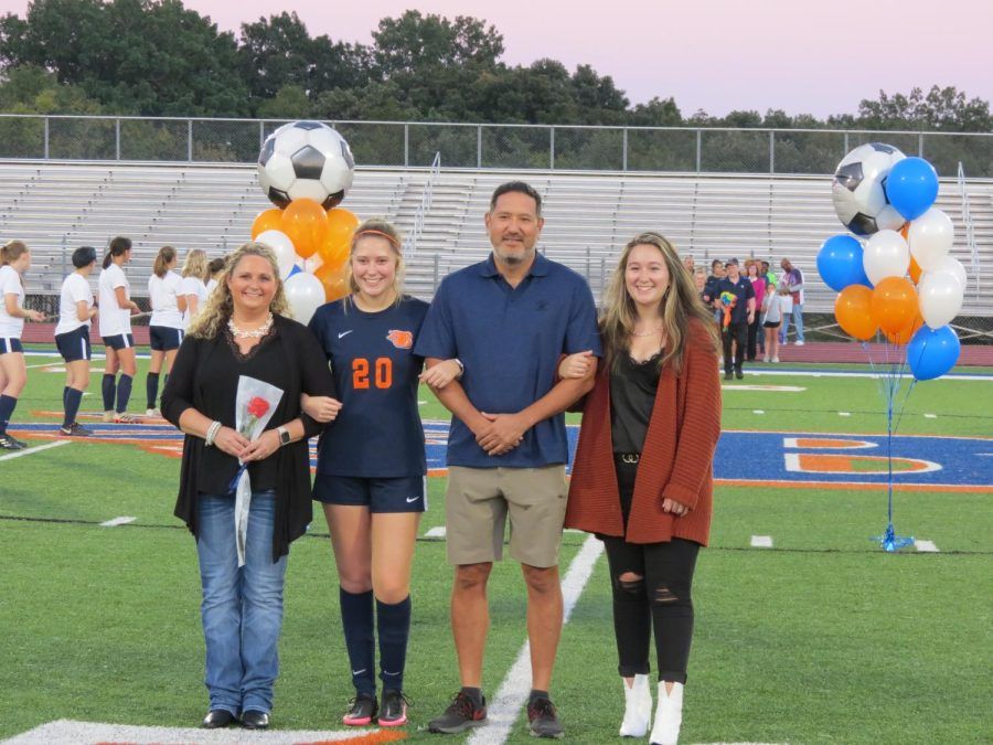 Senior Aleah Campbell is escorted by her parents and sister during Senior Night.