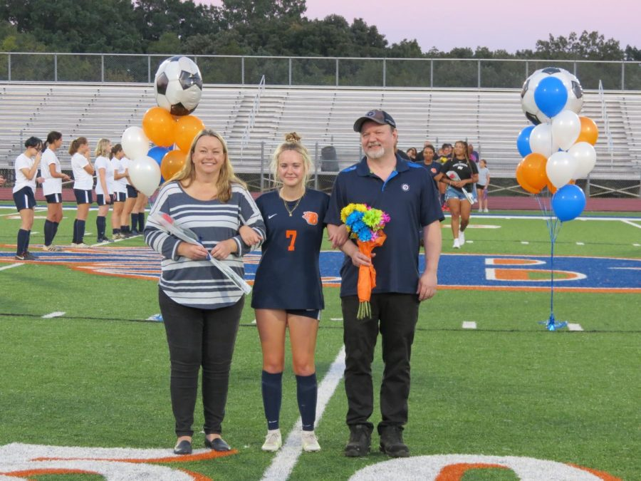 Senior Allyson Colson is escorted by her parents during Senior Night.
